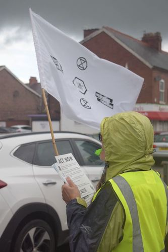 Person holding Act Now flyers whilst holding an Extinction Rebellion white flag,