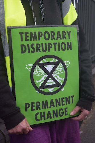 Person holding Extinction Rebellion poster reading Temporary Disruption, Permanent Change