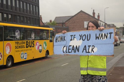Lady holding banner stating: honk if you want clean air
