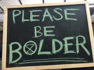 Placard stating Please be bolder