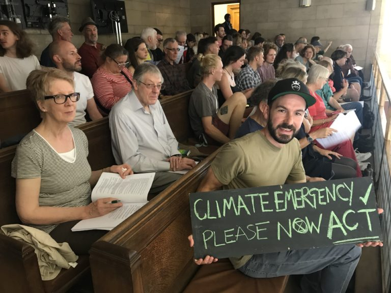 Campaigners at town meeting, one holding a sign saying Climate Emergency Please Now Act